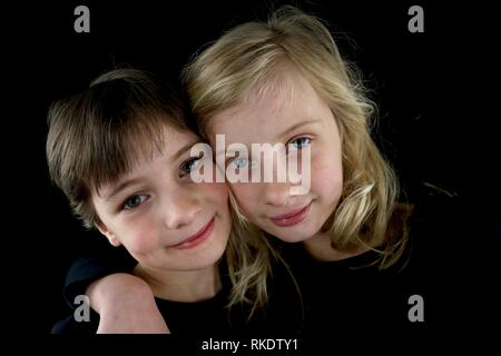 Portrait of two young sisters hugging each other - Stock Photo