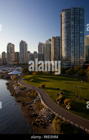 Multi-use recreation path winds along the shore of False Creek in Coopers Park, in Yaletown, Downtown Vancouver, British Columbia, Canada - Stock Photo