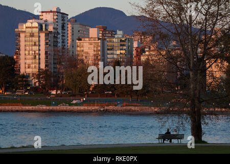 A man sits on a park bench in Vanier Park overlooking False Creek and Sunset Beach in Vancouver, British Columbia, Canada - Stock Photo
