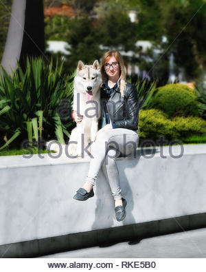 A grey Siberian husky male dog is sitting with young caucasian blond haired girl on marble floor. A woman wears black glasses, grey jeans, jacket. - Stock Photo