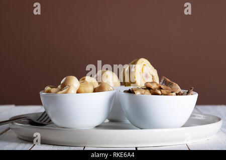 mushrooms and artichokes in oil in ceramic bowl on white wooden background. - Stock Photo