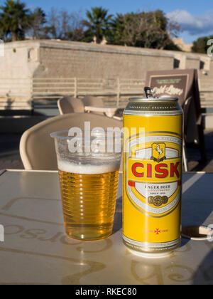 A can of the local lager beer brand Cisk and a plastic glass in an ope air bar in Malta with the city fortifications of Mdina in the background - Stock Photo