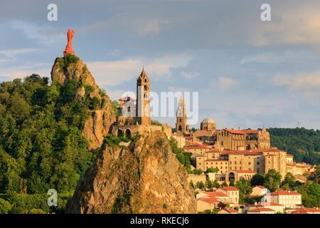 Statue of Notre Dame de France with Saint Michel d'Aiguilhe Chapel and Notre Dame Cathedral Le Puy en Velay Haute-Loire Auvergne-Rhône-Alpes France. - Stock Photo