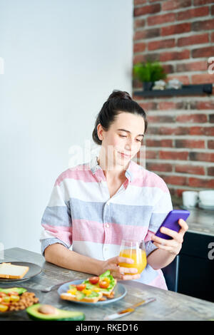 Checking Social Media at Breakfast - Stock Photo