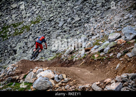 A man rides a mountain bike on a rocky trail in the Austrian resort of Sölden in the Ötztal Valley during the summer months. - Stock Photo