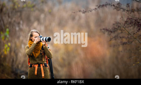 Pretty, female photographer taking pictures outdoor on a lovely autumn day - shallow DOF, color toned image