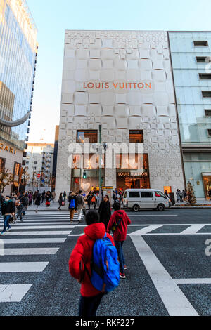 Tokyo, the Ginza. Foreground, people crossing on zebra crossing with the Louis Vuitton store building on other side of street. Daytime, golden hour. - Stock Photo