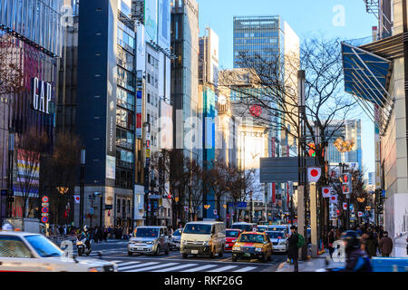 Tokyo, Ginza, golden hour. View along Chuo Dori shopping street from flagship store Gap at 4 chome towards Mitsukoshi store. - Stock Photo