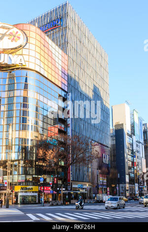 Tokyo, Ginza, golden hour. Flagship 4 level Gap store, largest in Japan, on Chuo Dori shopping street. Foreground, pedestrian crossing. - Stock Photo