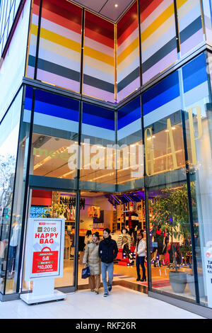 Tokyo, Ginza, daytime. Entrance to the flagship Gap superstore at Chome 4. Young Japanese smiling couple leaving store, passing a Happy Bag sign. - Stock Photo