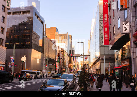 Tokyo, Ginza at golden hour. View along street and Matsuya and Apple stores. Pavement busy with shoppers. Illuminated christmas trees on sidewalk. - Stock Photo