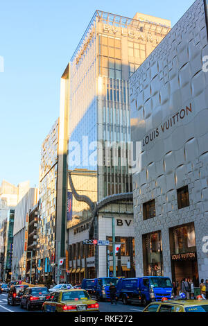 Tokyo, Ginza at golden hour. View along street, Louis Vuitton and the Bvlgari flagship store buildings with taxis waiting at red stop light in front. - Stock Photo