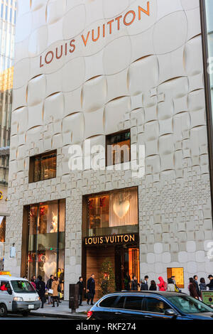 Tokyo, the Ginza, daytime. Louis Vuitton store building, illuminated window displays, Christmas tree outside entrance and people walking by. - Stock Photo