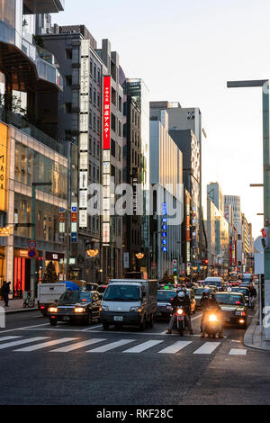 Tokyo, Ginza, golden hour. Traffic waiting at stop light in front of pedestrian crossing. View along street with high rise stores and buildings. - Stock Photo