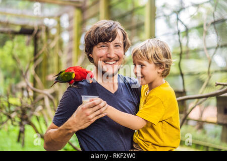 Ded and son feed the parrot in the park. Spending time with kids concept. - Stock Photo
