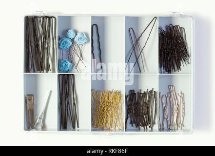 Fixing Hair Pins in a Plastic Box on White Background. - Stock Photo