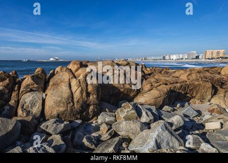 Rocky shore of Nevogilde civil parish of Porto, second largest city in Portugal. Port of Leixoes Cruise Terminal seen on background. - Stock Photo