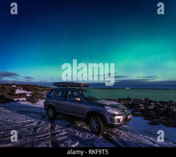 SUV car in the parking place under northen lights in Atlantic Ocean Road - Atlanterhavsvegen, in Norway. - Stock Photo