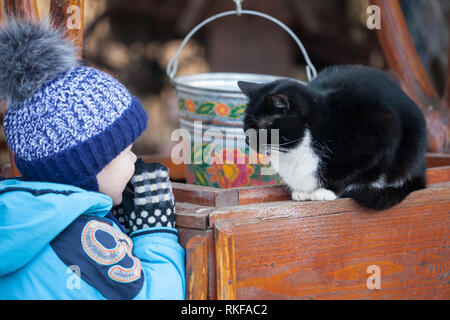 Little boy playing with a black cat. Black and white cat sitting on wooden well outdoors in the back yard - Stock Photo