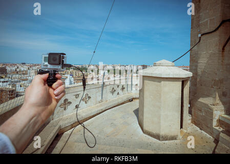 A man holds a GoPro camera in front of the view across the city at the top of the El Miguelete, the bell tower of the Valencia Cathedral, in Valencia, - Stock Photo