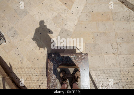 The feet and shadow of a man stood on a platform at the top of the El Miguelete, the bell tower of the Valencia Cathedral, in Valencia, Spain. - Stock Photo