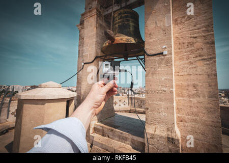 A man holds a GoPro camera in front of a large bell at the top of the El Miguelete, the bell tower of the Valencia Cathedral, in Valencia, Spain. - Stock Photo