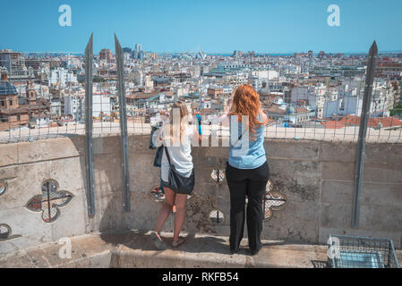 Two women take photographs and admire the view of the city from the top of the El Miguelete, the bell tower of the Valencia Cathedral in Valencia, Spa - Stock Photo
