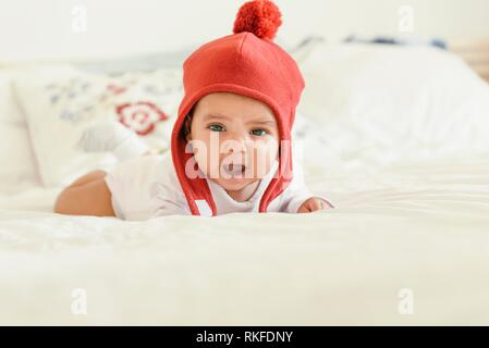 Cute Baby Girl Crying in the Crib. At home. - Stock Photo