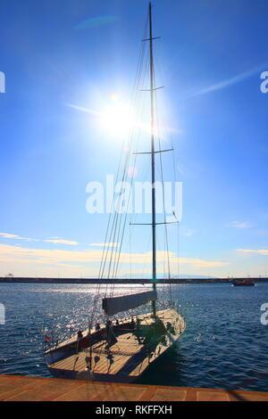 Sailing boat in prot of Rijeka, Croatia; sun on blue sky in background - Stock Photo