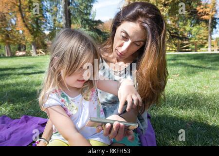 Four years age blonde girl pointing with finger screen of smartphone, and talking to woman mother, sitting on green grass in park of Retiro, in - Stock Photo