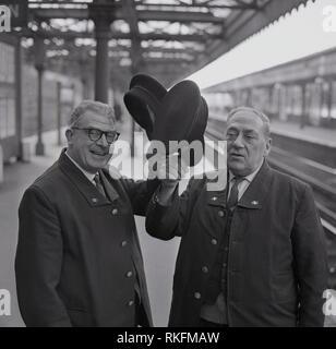 1968, two cheerful uniformed British Rail station staff, a foreman and ticket collector standing on a platform at Blackheath railway station, raise their caps, Blackheath, London, England, UK. - Stock Photo