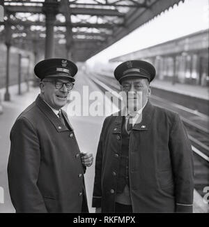 1968, picture shows two cheerful uniformed British Rail staff, a station foreman and ticket collector standing together on the platform at Blackheath railway station, Blackheath, London, England, UK. - Stock Photo