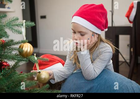 funny scene: four years blonde cute girl with red Santa Claus hat, holding a golden ball in Christmas tree, resting on her mother back, at home. - Stock Photo