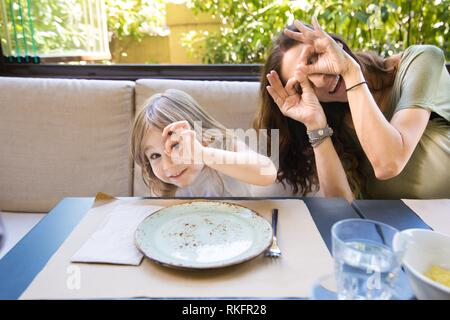 Funny family expression and gesture. Four years age blonde happy girl woman mother teasing and grimacing with fingers in eyes sitting in restaurant. - Stock Photo