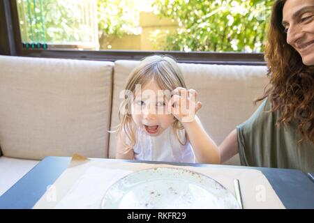 Funny expression and gesture. Four years age blonde happy girl teasing and grimacing next to woman mother smiling sitting in restaurant. - Stock Photo