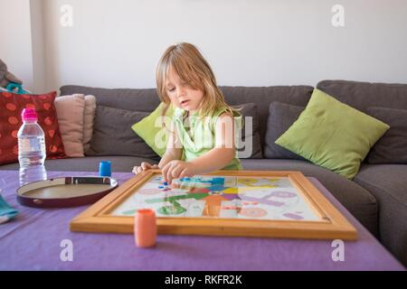 four years old blonde child with green sleeveless shirt sitting on brown sofa, playing parcheesi or parchisi or parchis, on table. - Stock Photo