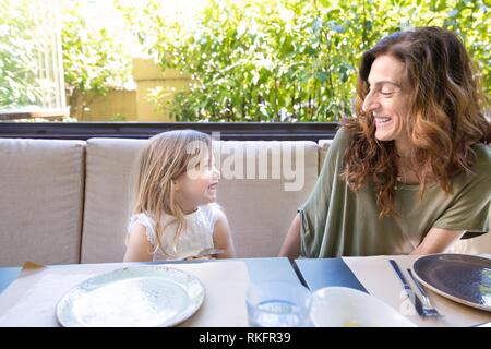 woman mother and her daughter four years old blonde girl laughing with funny face expression, happy family sitting in restaurant. - Stock Photo