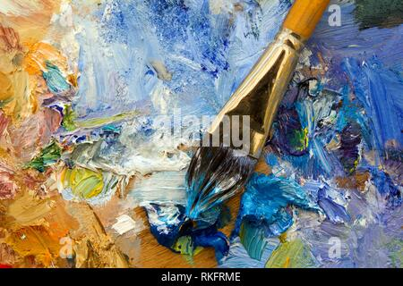 Multi-coloured artists oil paint palette and paintbrush. - Stock Photo