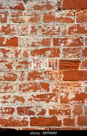 An old weathered, damaged, formerly painted, badly repaired red brick wall full frame background. - Stock Photo