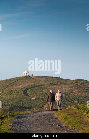 A mature couple enjoying walking along the South West Coast Path during the evening sunlight at Newquay Cornwall. - Stock Photo