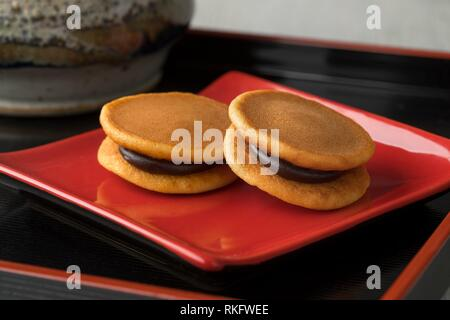 Two Japanese Dorayaki close up on a red dish. - Stock Photo