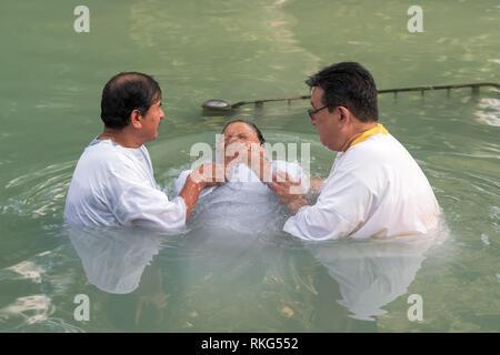Yardenit, Israel - 29 December 2012: Unidentified christian pilgrim woman gets baptised in the Jordan River in North Israel (Yardenit Baptismal Site). - Stock Photo