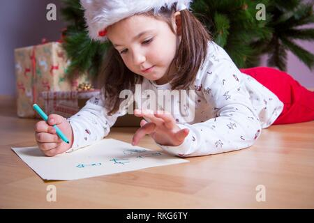 Little girl preparing the Santa Letter. She painting the gifts she want. Pre-reader concept. - Stock Photo