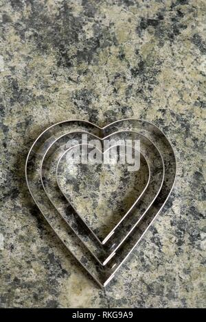 A set of three heart shaped cookie cutters on a marble effect kitchen surface. - Stock Photo