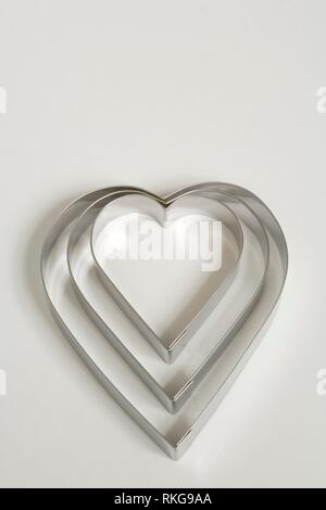 A set of three heart shaped cookie cutters on a white background. - Stock Photo