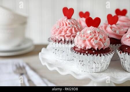 Red velvet cupcakes decorated with red hearts. - Stock Photo