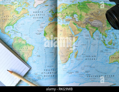 Lined Notebook with White Pencil and Camera on the World Map