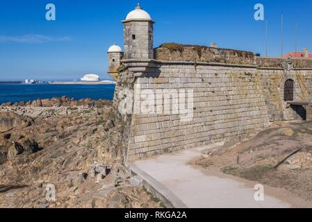 Fort of Sao Francisco do Queijo also knows as Castle of the Cheese in Porto, Portugal. Port of Leixoes new Cruise Terminal building on background. - Stock Photo