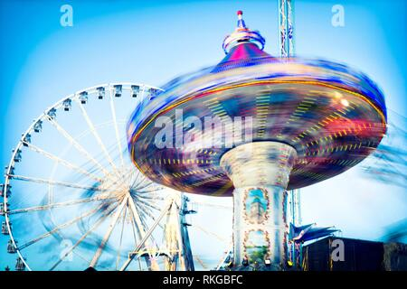 Close-up of Chair Swing ride with unrecognizable people in motion. Winter Wonderland, Hyde Park, London, UK, Europa. - Stock Photo