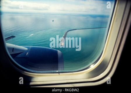 View from airplane window. View of containership leaving the port of Barcelona. Barcelona, Catalonia, Spain. - Stock Photo